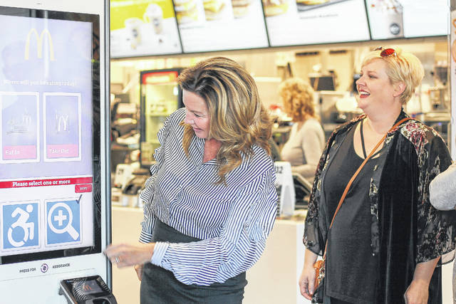 Sidney McDonald's owner Stacy Scott shows how to work the new kiosk as Amy Breinich, Sidney Alive director, looks on.