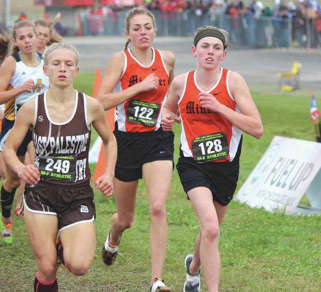 Minster's Emma Watcke, right, and Kaitlynn Albers, center, run in the Division III girls state cross country race on Saturday at National Trail Raceway in Hebron. The Wildcats won the D-III title for the second consecutive season. Greg Billing | Sidney Daily News