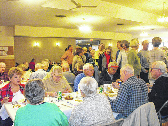 The line snakes through the dining hall and out the front door during the annual Thanksgiving Dinner in the Knights of Columbus hall in Minster, Thursday, Nov. 23. The holiday celebration was open to anyone who wanted to attend. Organizers said 420 meals were served.