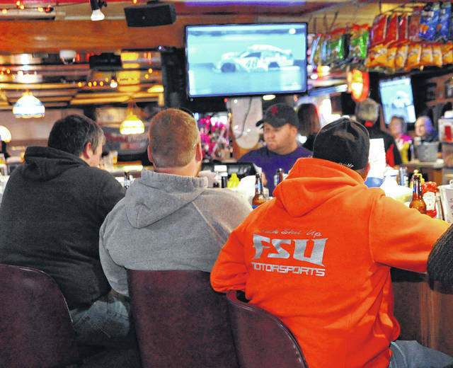 Zach Gibson, left to right, backs to camera, Josh Keith and Andy Limbert, all of Wapakoneta, watch auto racing instead of NFL football in Meyer's Tavern in Botkins, Sunday, as tavern manager Josh Meyer works the bar. The tavern joined a nationwide boycott of NFL games during Veterans Day weekend.