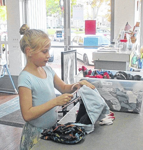 A young volunteer prepares clothing for display at the Right to Life thrift shop.