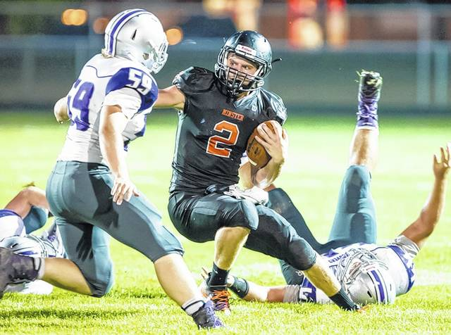 Minster's Jared Huelsman dodges Fort Recovery players during a game at Minster in September. The Wildcats lost four consecutive games in Midwest Athletic Conference play for the second-straight season but are in the Division VII state championship game again.