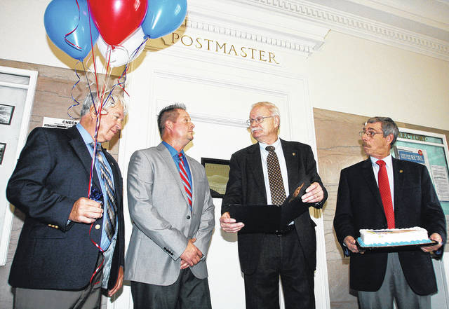 Sidney Mayor Mike Barhorst, third from left, finishes reading a proclamation to Sidney Postmaster Brian Schroeder, second from left, of Anna, to recognize the 100th anniversary of the Sidney Post Office building. Sidney council members Ed Hamaker, left, and Steve Wagner, brought balloons and cake to the ceremony held Monday, Nov. 6.