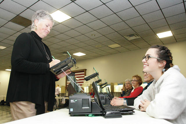 Lisa Hoewischer, left, at an E-poll Book manned by Ariana Bolin, both of Sidney, at the Sidney VFW located polling station Tuesday, Nov. 7.