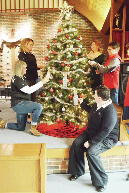 POWER members, clockwise, POWER Chair Connie Barhorst, POWER Associate Amy West, Power members Susan Molon and Jennie Rogers, decorate a tree with Salvation Arm Lt. Chastity Hansen, all of Sidney, with Salvation Army Angel Tree donation cards Tuesday, Nov. 21. The POWER representatives came to the Sidney Salvation Army to donate $1,000 to the Salvation Army Angel Tree program. Salvation Arm Lt. Chastity Hansen met with the POWER members to recieve the donation. POWER is a United Way Women's initiative group. POWER has helped fund the Angel Tree program fo the past 3 years. The Angel Tree program provides new clothing to children in need.