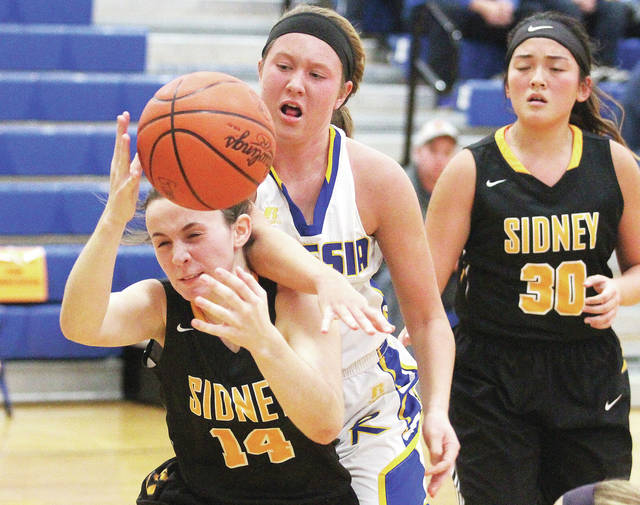Sidney's Hallie Truesdale, right, works to keep the ball from Russia's Jenna Cordonnier, middle, during a season opener on Friday at Russia.