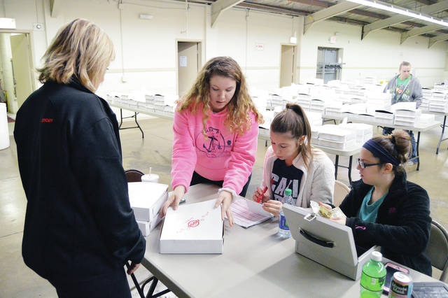Heather Bensman, left to right, of Anna, is presented with her three pre-ordered The Spot pies by Madisyn Allen, 16, of Sidney, daughter of Brandy and Jason Allen, as Keaton Eilert and Myracle Blosser, all of Sidney, mark the pies off their list and take payment. The annual The Spot pie sale was held at the Shelby County Fairgrounds Wednesday, Nov. 22, just in time for Thanksgiving.