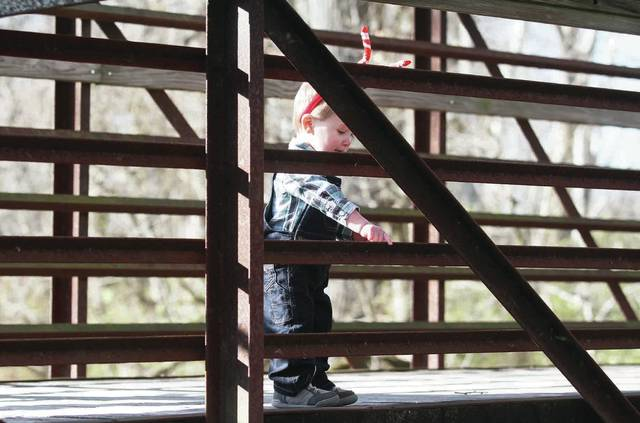 Cohen Cecil, 1, of Botkins, son of Brooke and Channing Cecil, takes a brake from his families Christmas themed photo shoot to look down at the water flowing under the Davis Bridge in Tawawa Park Sunday, Nov. 26.