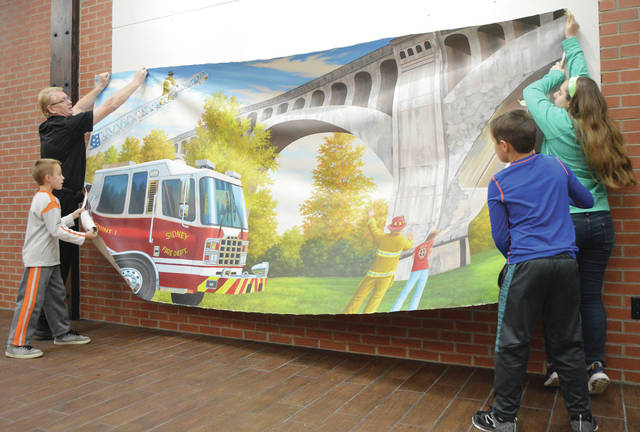 Firehouse Subs owner Tom Martin, upper left, of Sidney, gets help from his kids, Monday, Nov. 28, in holding up a hand-painted mural, where it will be mounted and framed on the wall of the new restaurant in Sidney Towne Center along West Michigan Street. The kids, left to right, are Bobby Martin, 10, Brandon Martin, 10, and Isebelle, 14, all of Sidney, all also children of Becky Martin. The painting depicts Sidney Fire Department's Lt. Jason Truesdale showing Becky Martin the Big Four Bridge and the Sidney Fire Department's Quint 1 firetruck. Truesdale took Martin around Sidney to take pictures for subject material for the mural. The Martins sent a photo of the Quint 1 and the Big Four Bridge to the Firehouse Subs headquarters in Florida where artist Joe Puskas and his team painted the mural using the photos.