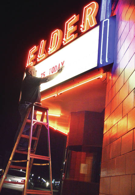 "Rodney Miller, of Jackson Center, puts ""75 Today"" on the marquee of the Elder Theater in Jackson Center, Tuesday, Nov. 28, to let everyone know how long the popular local spot has been a gathering place for local movie-goers. Miller and his wife, Becky, have owned the theater since 1982."