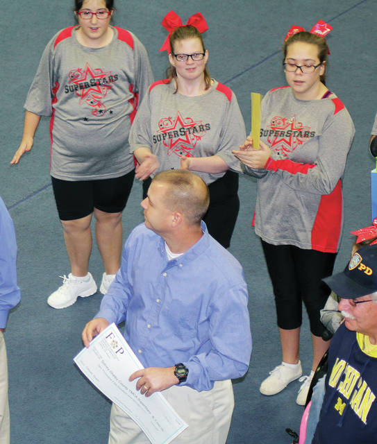 Fraternal Order of Police Gateway Lodge No. 138 members Rodney Robbins, front center, and Vic Elliot, bottom right, get a round of applause from SuperStar cheerleaders, left to right, back, Emma Weaver, of Troy, Alyssa Clason, of Sidney, and Sarah Snider, of Botkins, at the Sidney-Shelby County YMCA, Monday, Nov. 27. The SuperStar cheerleaders performed a cheer after the FOP donated money to their program. The FOP has backed the YMCA SuperStar program for three years.