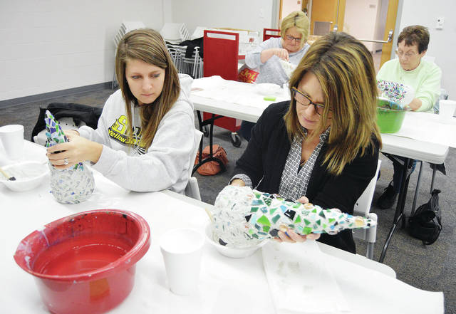 Making Christmas trees out of stained glass shards at the Amos Memorial Public Library, Tuesday, Nov. 28, are, left to right, front, Jordyn Trabue, of Sidney, Jenny Luebke, of Minster, Back row, Cindy Maurer and Sue Fair, both of Sidney. The art class was taught by local artist Kelly Walker.