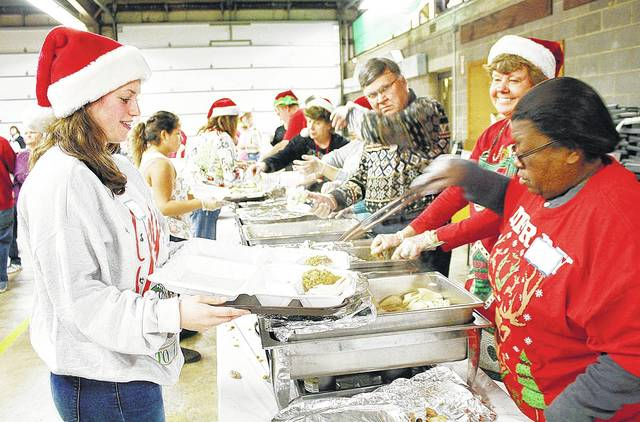 Ashley Keller, left to right, waits for David Fogt, Becky Michael and Jerri Wooten, all of Sidney, to fill up the tray she will deliver to someone who couldn't stand in line at the 2016 Community Christmas Dinner. Keller said then helping at the dinner is a family tradition.