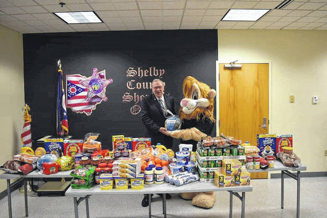 Shelby County Sheriff John Lenhart and Daren, the DARE lion, sort food for gift baskets for three needy families. The food was purchased with funds raised by DARE students at several schools.