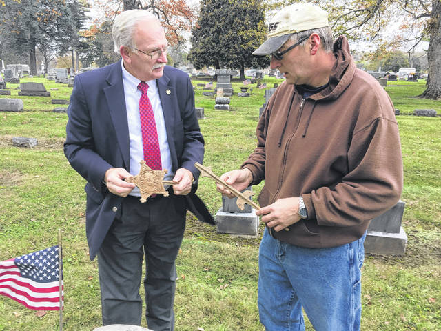 Mark Smith, of Gravestone Transformations, shows Sidney Mayor Mike Barhorst an original, cast iron, veteran's flag holder issued to members of Grand Army of the Republic Neal Post 62. The Civil War-era marker was found at the grave of Thomas Robbins when his gravestone was removed for restoration.