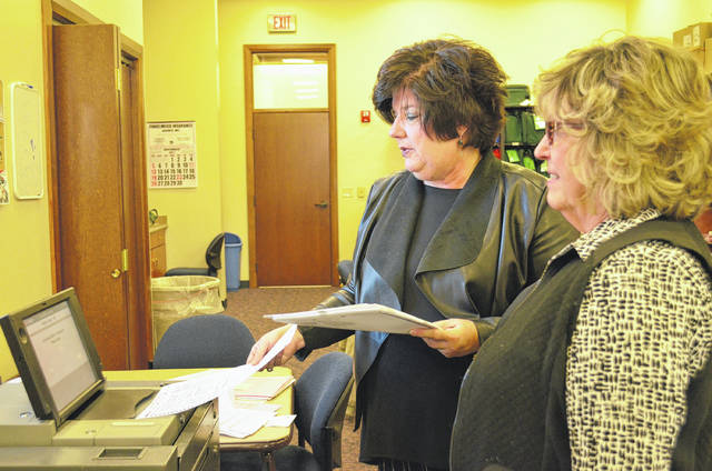 Michelle Wilcox, director of the Auglaize County Board of Elections, and Peggy Matheny, deputy director, feed election night ballots from the New Bremen West precinct into a DS200 optical scanner while performing a recount for the New Bremen Local Board of Education race Tuesday at the Auglaize County Board of Elections office.