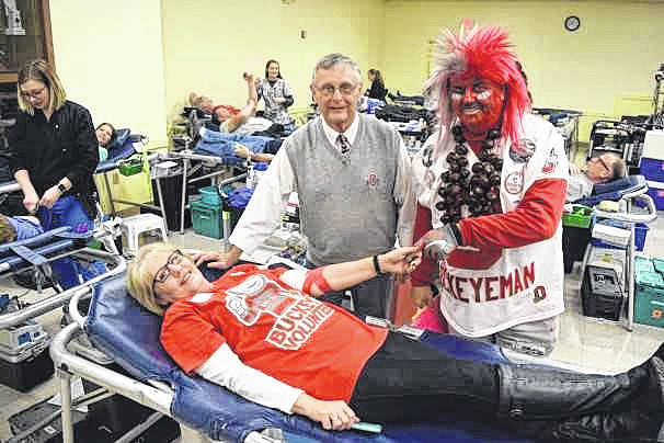 OSU Alumni Association member Helen Ward donates blood during the organization's recent blood drive as Jim Singleton, dressed as former OSU Coach Jim Tressel, and Buckeyeman Larry Lokai look on in the American Legion post in Sidney.