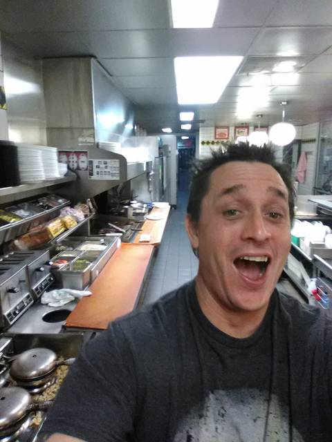 In this image taken early Thursday, Nov. 30, 2017, Alex Bowen poses in the kitchen at a Waffle House in West Columbia, S.C. When Bowen found the only worker at the empty South Carolina Waffle House asleep, he took his meal into his own hands. Bowen chronicled with selfies how he made his own double Texas bacon cheese steak melt on Facebook
