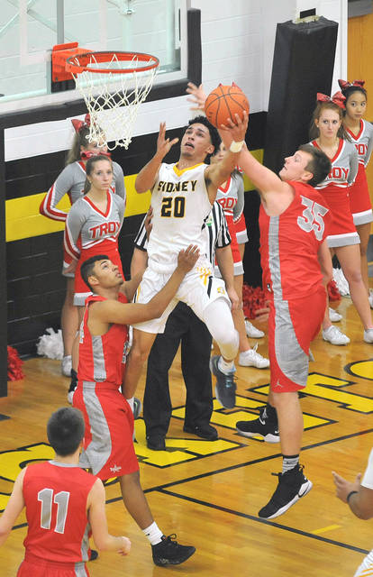 Sidney junior Andre Gordon, center, shoots with pressure from Troy's Adam Gates, right, and Brenden Kinnel, left, during a Greater Western Ohio Conference game on Tuesday.