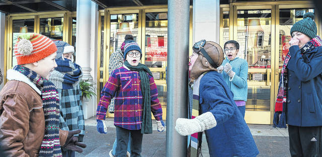 "Children in the cast of ""A Christmas Story"" at the Victoria Theatre in Dayton re-enact a scene along a Dayton street recently."