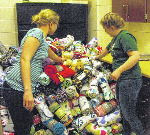 Emma Ewry, 14, left, daughter of Shelly and Patrick Ewry, of Wapakoneta, and Sarah VanBrocklin, 16, daughter of Dena and Michael VanBrocklin, of Botkins, add stuffed toys to a pile of fleece blankets in the family and consumer sciences classroom at Botkins High School, Monday, Dec. 4. The girls are collecting funds for stuffed toys to donate with the blankets to patients at Dayton Children's Hospital. The project is for an FCCLA competition.