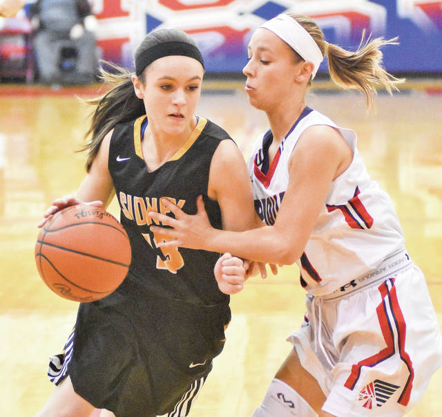Sidney's Carrie Nuss, left, dribbles with pressure from Piqua's Kayli Smith on Friday at Garbry Gymnasium in Piqua.