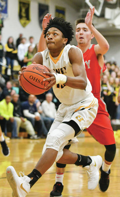 Sidney junior forward Ratez Roberts drives to the basket with pressure from Troy's Eli Palmer during a Greater Western Ohio Conference game on Tuesday.