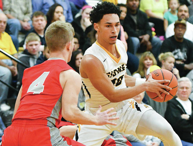 Sidney junior guard Andre Gordon dribbles around Troy's Brayden Siler during a Greater Western Ohio Conference game last Tuesday. Sidney hosts Butler this Tuesday in a key GWOC North contest.