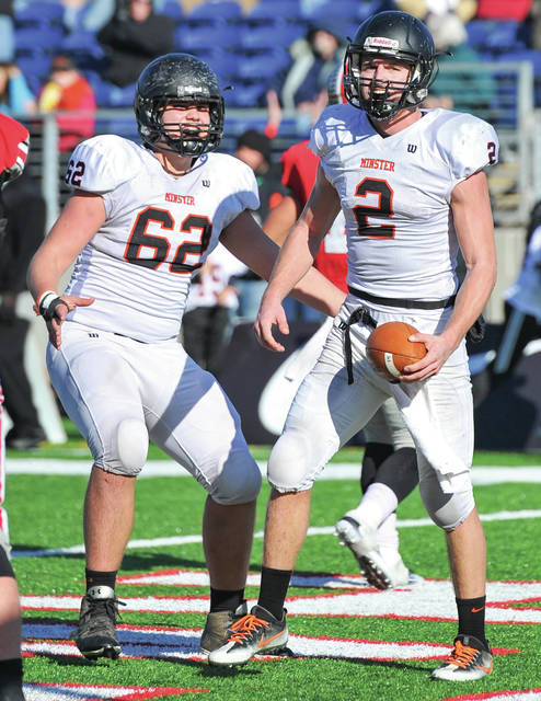 Minster quarterback Jared Huelsman, right, and offensive line Sam Schmiesing celebrate after a touchdown at the end of the second quarter.