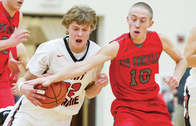 Fort Loramie's Dillon Braun, right, dribbles as New Knoxville's Ben Lammers reaches for the ball during a nonconference game on Saturday.