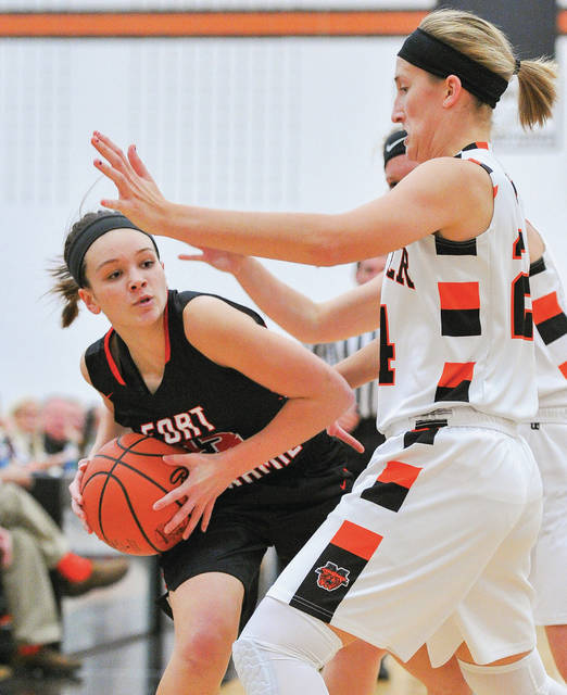 Fort Loramie's Taylor Ratermann tries to pass around Minster's Taylor Kogge during a nonconference game on Tuesday at Minster.