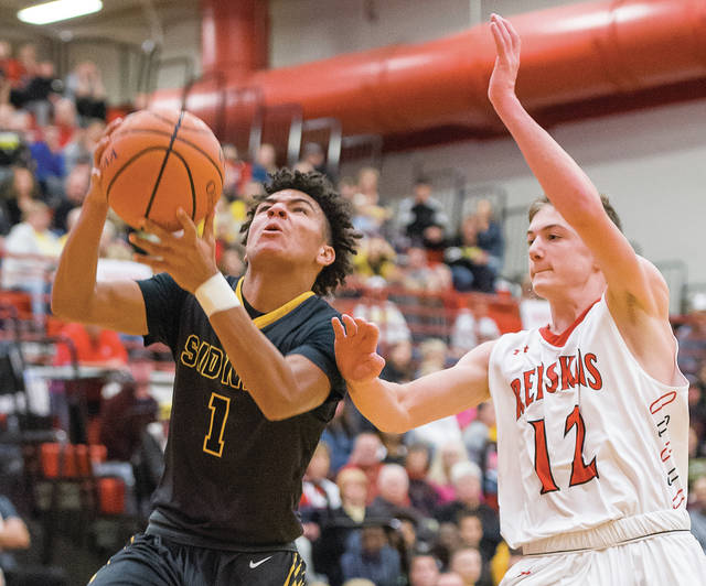 Sidney's Darren Taborn drives to the basket ahead of Wapakoneta's Reed Miracle during a nonconference game on Saturday in Wapakoneta.