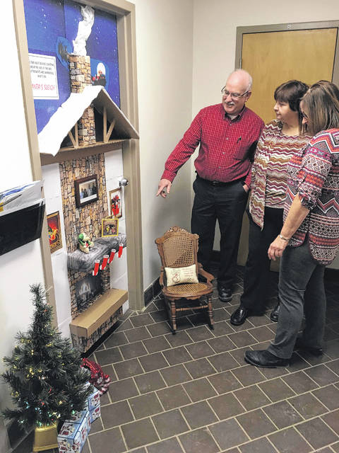 Utilities Director Bill Blakely points to the fire burning brightly in the fireplace as Human Resources Manager Vicki Allen and Service Center Secretary Joyce Reier look at the framed photo of members of the department hung above the mantle. The door garnered first place in the City's Christmas Door Decorating Contest.