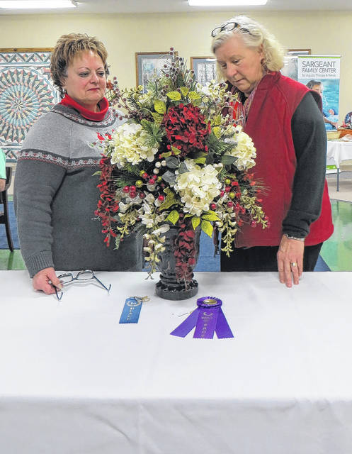 Teresa Freisthler, of Sidney, left, discusses her flower arrangement with judge Marian Moeckel, of Troy, during the Rainbow Gardeners' Christmas flower show at Ohio Living Dorothy Love, recently.
