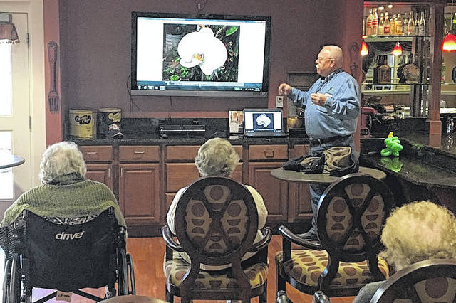 Duane Mullen, of Sidney, talks about a photo of a flower, taken on one his many trips throughout the United States, during a presentation recently at Elmwood Assisted Living in New Bremen.