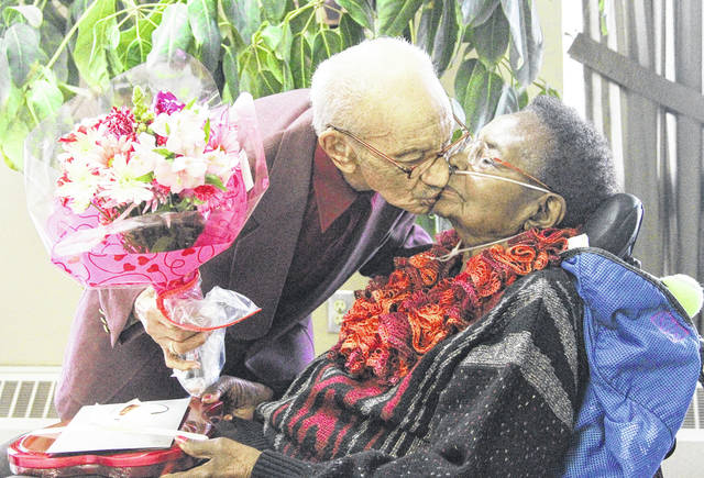 Hume Merritt, left, surprises his wife of 76 years Jessie Merritt, both of Sidney, with chocolates and flowers at FairHaven Tuesday, Feb. 14. They were both attending the FairHaven Valentine's Day dinner.