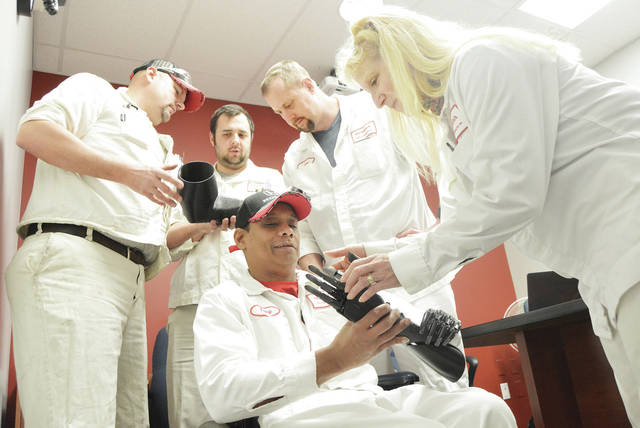 Tony Leonard, left, front looks at a prothstetic arm with Honda Engineering employee Susie Bowles, of Sidney, who helped make the arm along with fellow Honda employees, left to right, back, Richard Crosson, of Anna, Corey Howard, of Raymond, and Les Bowers, of Wapakoneta.