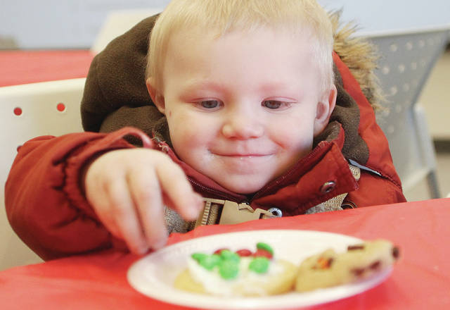 COUNTDOWN TO CHRISTMAS: There are 21 days until Christmas. Syrus Richards, 2, of Sidney, son of Kevin and Clorissa Richards, reaches for a Christmas cookie, freshly frosted by his dad at the Amos Memorial Public Library's Holiday Open House event, Saturday, Dec. 3, in Sidney. Kids could sit on Santa's lap while musicians performed Christmas music, pet a live reindeer and make a variety of crafts. See Wednesday's Sidney Daily News for photos of other area holiday events that took place Saturday and Sunday.
