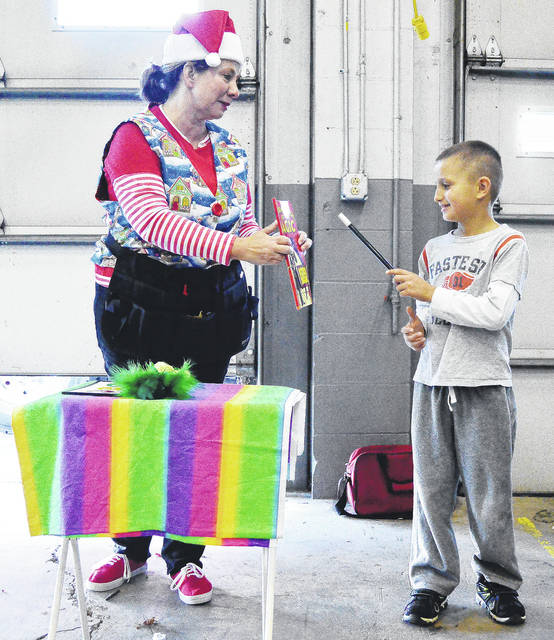 Tina Alt, left, of Versailles, gets some help performing a magic trick from Caden Platfoot, 7, of Botkins, son of Tom and Holly Platfoot. Besides a magic show kids could play games and visit Frosty at the Botkins Fire Department, Sunday, Dec. 3.