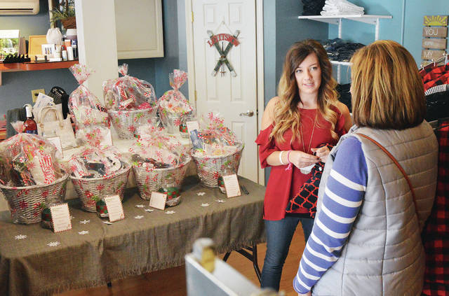 Small Town Boutique owner Abbey Goubeaux, left, of Minster, talks with customer Heidi Heuing, of Russia, during a holiday open house for the boutique, in Fort Loramie, Sunday, Dec. 3. Behind Goubeaux are baskets she is raffling off until the end of December. All the money raised from the raffle will go to buy toys for kids at the Dayton Children's Hospital. Goubeaux got the idea for the raffle after her father was diagnosed with small cell aggressive lung cancer in June. Goubeaux hopes to personally deliver the presents to the kids at Dayton Children's Hospital.