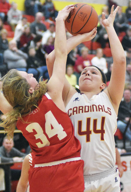 New Bremen's Kayla Bergman shoots as St. Henry's Nora Vaughn slaps at the ball on Thursday.