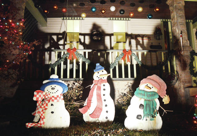 Some warmly dressed snowmen sit in the front yard of a house on Fair Road, Wednesday, Dec. 6.