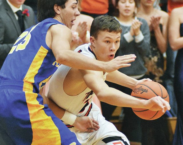 Jackson Center's Trent Platfoot drives against Russia's Jack Dapore during a Shelby County Athletic League game on Friday in Jackson Center. Platfoot led Jackson Center with 11 points.
