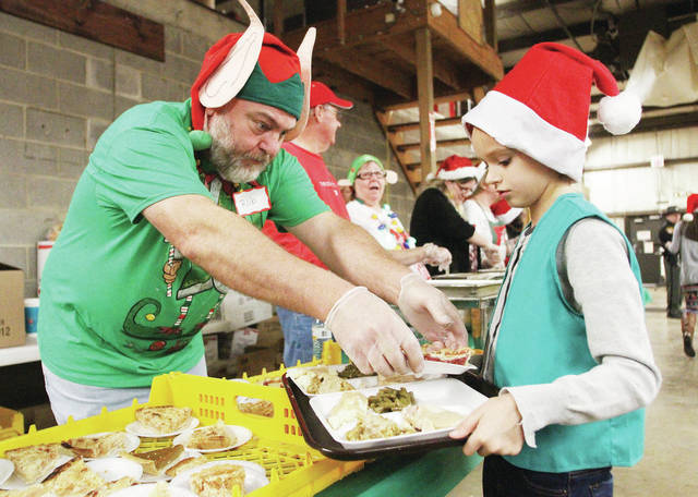 COUNTDOWN TO CHRISTMAS: There are 14 days until Christmas. Rob Smith, left, of Anna, puts a piece of pie on a tray held by Kaylee Morgan, 9, of Sidney, daughter of Josh and Kristen Morgan, at the 2017 Shelby County United Way Community Christmas Dinner. The free dinner was held at the Civil Defense Building Saturday, Dec. 9. The Anna Jazz Band performed while Santa talked with kids waiting in line for food. Kaylee was at the dinner with her Girl Scout Troop 20319 as a volunteer helping to bring people who couldn't stand in line their food.