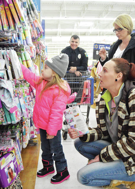 Cyrenity Hatcher, left to right, 4, picks out clothes as Sidney Police Officer Nick Zimmer, Cyrenity's mom Crystal Hatcher, and Zimmer's wife Tiffani Hatcher, look on at Walmart, Sunday, Dec. 10. Cyrenity was getting help picking out clothing from Zimmer as part of the annual Shop with a Cop program. Cyrenity is also the daughter of Michael Hatcher.