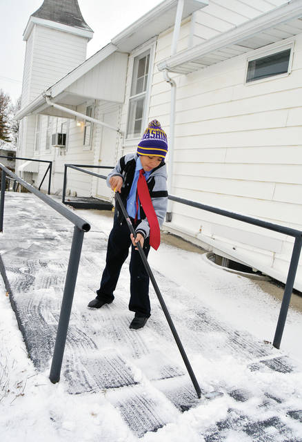 Kyrese Leslie, 7, of Sidney, son of Doug Leslie, sweeps snow off a ramp at the Mt. Vernon Baptist Church Sunday, Dec. 10. A small accumulation of snow Saturday, Dec. 9, made for slow driving in the afternoon.