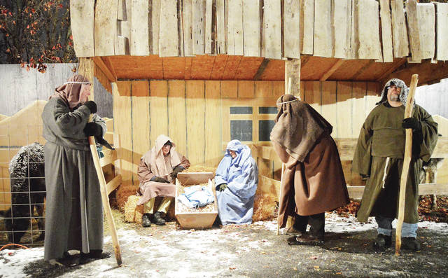COUNTDOWN TO CHRISTMAS: There are 12 days until Christmas. Taking part in the First Church of the Nazarene's Live Nativity Drive-Through are, left to right, Tim Gotshall, as a wise man, Paul Snyder, as Joseph, Jaenise Exley, as Mary, and Jo Anderson and Scott McDonald, as wise men. All are from Sidney. The annual live nativity included live animals and scenes from the Bible about Jesus' birth. Also depicted were people filling an Agape truck with food and Santa praying under a cross.