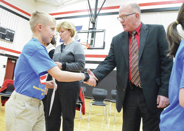 A.J. Siegel, left, 10, of Fort Loramie, shakes the hand of Shelby County Sheriff's Chief Jim Frye during the Drug Abuse Resistance Education (D.A.R.E.) 2017 fall session graduation ceremony. The ceremony was held at Fort Loramie Elementary Wednesday, Dec. 13. Fort Loramie teacher Carla Siegel, of Fort Loramie, second from left, helps hand out certificates. Fifth graders from Botkins, Jackson Center and Hardin-Houston Schools also graduated from the program that is run by Shelby County Sheriff's Office Deputy Brian Strunk. Attending the event were Shelby County Commissioner's Bob Guillozet, Tony Bornhorst and Julie Ehemann. The 13 week class graduated 219 students.