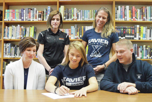 Cassie Francies, center, signs a letter of intent to run track for Xavier. Watching Francis sign are, left to right, her mother, Jenni Francis, Minster High School assistant coach Molly Watcke, Minster track and field and cross country head coach Jessie Magoto and Francis' father Greg Francis. Francis signed the letter of intent in Minster High School's library on Thursday.
