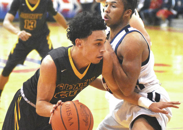 Andre Gordon advances against a Piqua defender on Friday. Gordon led the Yellow Jackets with 23 points.